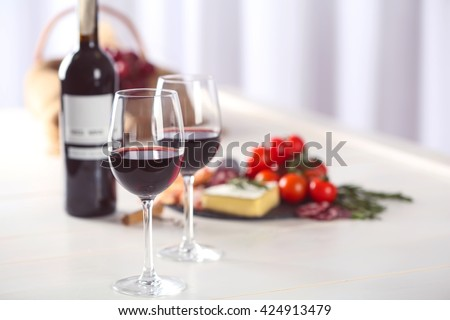 Glasses of red wine with food on blurred background - stock photo
