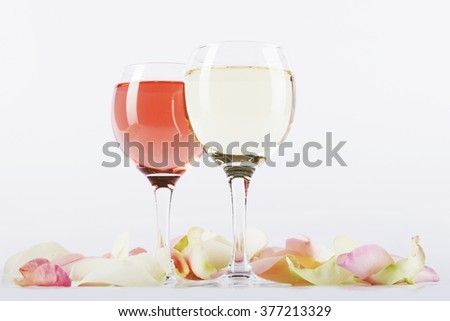 Glasses of rose and white wine surrounded by rose-petals - stock photo