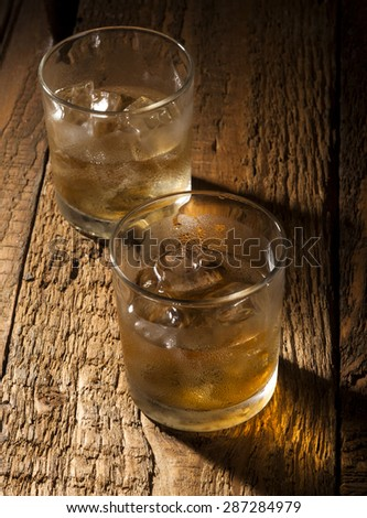Glasses of scotch on wooden vintage background with copyspace.