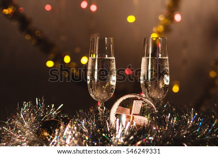 Glasses of sparkling champagne on table in the house against the colorful burning gerlyand in romantic holiday setting
