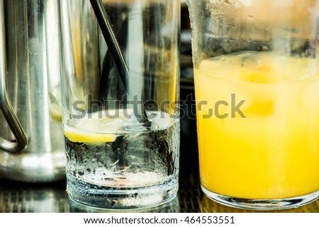 Glasses of Still Mineral Water and Orange Juice Half Drunk With a Straw Iced and Lemon