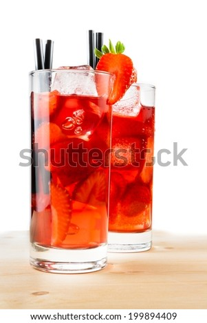 glasses of strawberry cocktail with ice on light wood table and a white background - stock photo