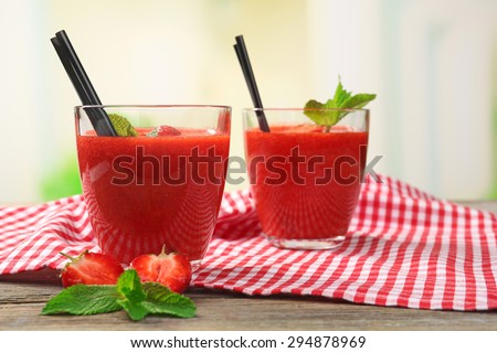 Glasses of strawberry smoothie with berries on bright background - stock photo