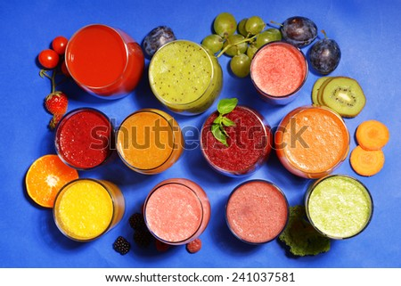 Glasses of tasty fresh juice, on blue background - stock photo