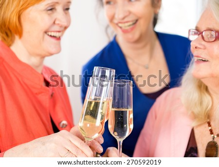Glasses of Tasty White Wine Tossed by Happy Adult Lady Friends to Celebrate Something. - stock photo