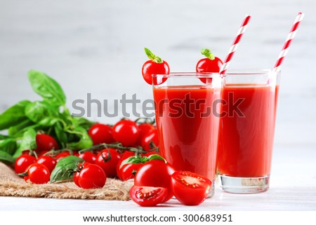 Glasses of tomato juice with vegetables on wooden table background