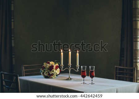 Glasses of vine, candles and flowers for romantic evening - stock photo