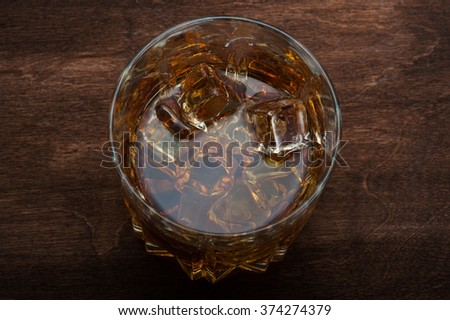 Glasses of whiskey on dark wood background