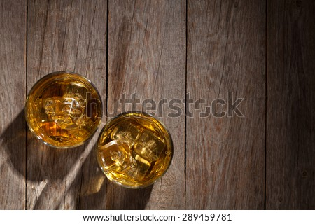 Glasses of whiskey with ice on wooden table. Top view with copy space - stock photo