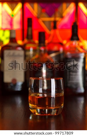 glasses of whisky on a dark wooden table in the background with a bottle of whiskey - stock photo