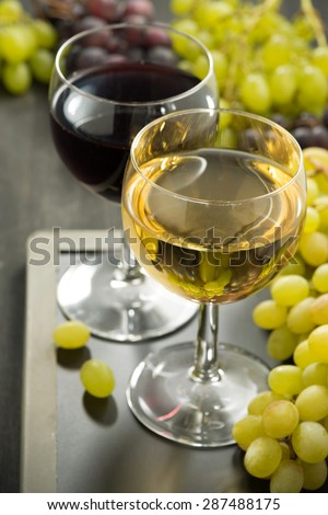 glasses of white and red wine and grapes on a blackboard, close-up, vertical - stock photo