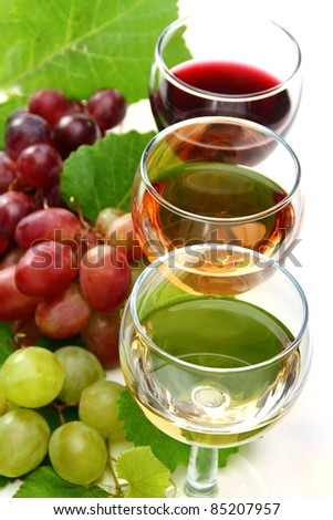 Glasses of white, pink, red wine and grape on white background. - stock photo