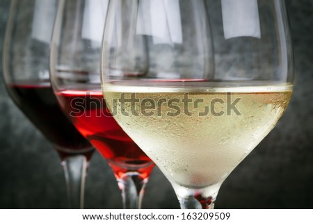 Glasses of white, rose and red wine.  Focus on foreground. - stock photo