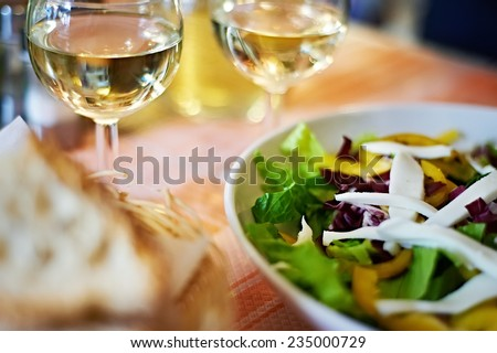 Glasses of white wine and a salad on the table cafe - stock photo