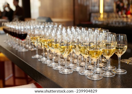 Glasses of white wine on bar counter, small focus depth - stock photo