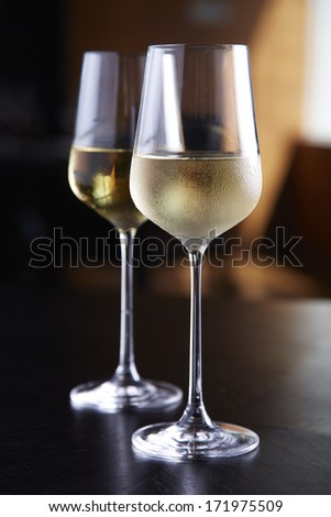 Glasses of white wine on table - stock photo