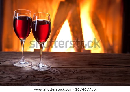 Glasses of wine and a fireplace fire. - stock photo