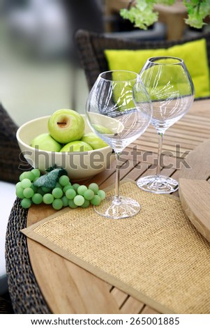 Glasses of wine and a fruit plate on the table - stock photo