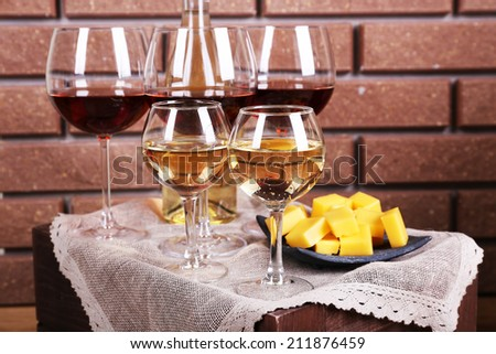 Glasses of wine and cheese on table on brick wall background - stock photo
