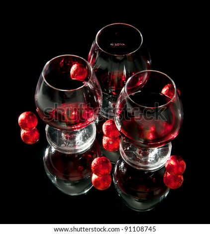 Glasses of wine and chocolate on a black background