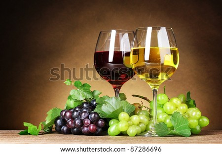 Glasses of wine and grapes on yellow background - stock photo