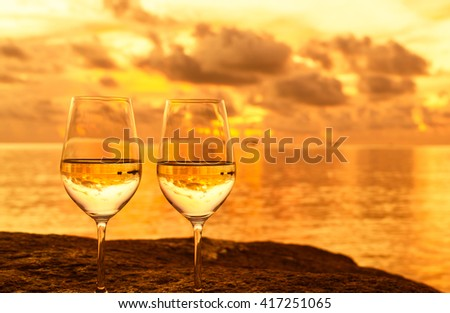 Glasses of wine in a beautiful sunset setting.  - stock photo