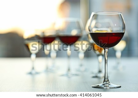 Glasses of wine on light blurred background - stock photo