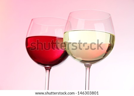 Glasses of wine on light pink tone