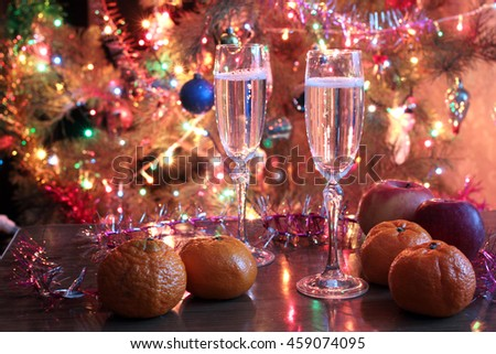 Glasses of wine, tangerine and apple on Christmas table