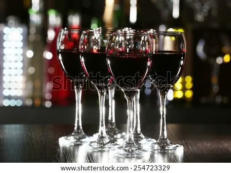 Glasses of wine with bar on background