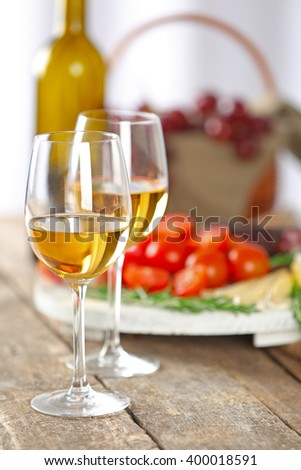 Glasses of wine with food on wooden table closeup