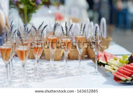 Glasses of with pink champagne decorated with lavender - stock photo