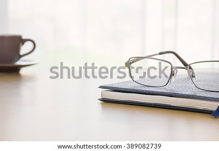 Glasses on a book with on the desk by nature background - stock photo