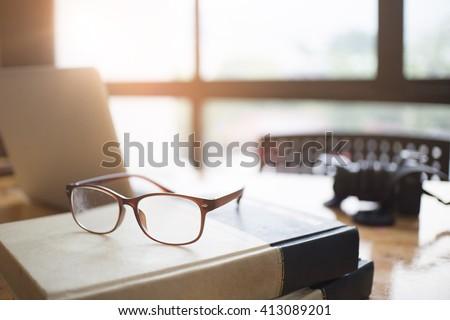 glasses on book,morning light effect. - stock photo
