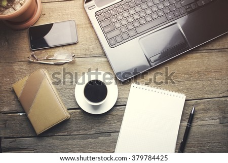 glasses on computer, cup of coffee and paper on wooden table
