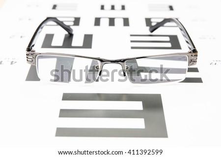 Glasses on eye chart - stock photo