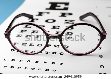 Glasses on eye chart background, close-up - stock photo