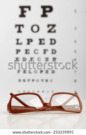 Glasses on eye chart background, close-up - stock photo