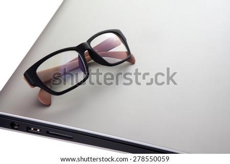 Glasses on laptop computer white background - stock photo
