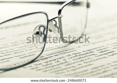 Glasses on newspaper. Toned