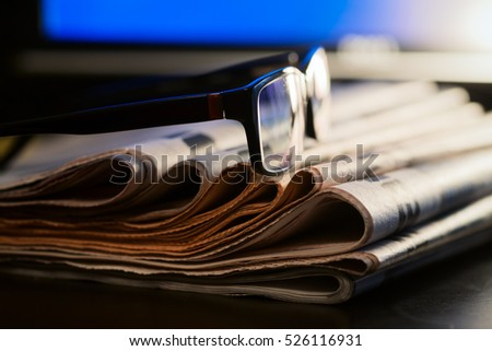 Glasses on stack of newspapers with blurred screen in background - News concept