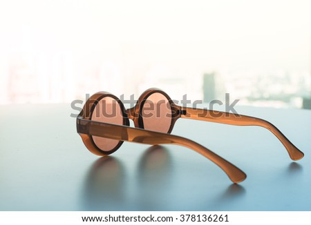 Glasses on table with window view  in vintage color style for summer or vacation concept/selective focus - stock photo