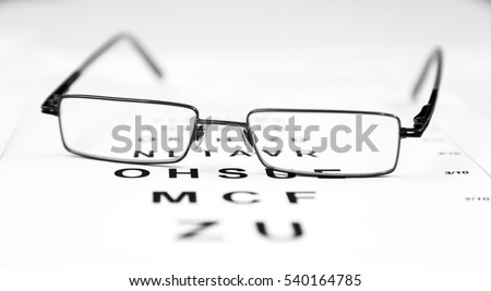 Glasses on test chart.Eye chart extreme closeup.Eyes Examination, glasses diopter check up.Clear Black modern glasses on a eye sight test chart.