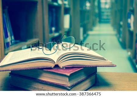 Glasses on the books in library with library blurred background, Education concept - stock photo