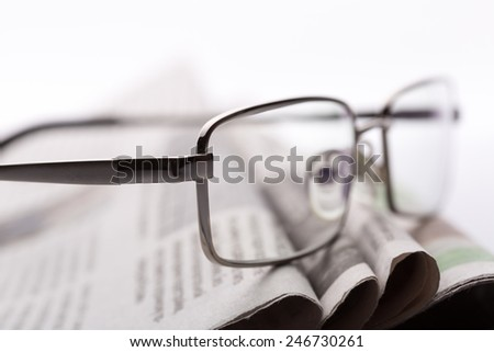 Glasses on the newspapers closeup - stock photo