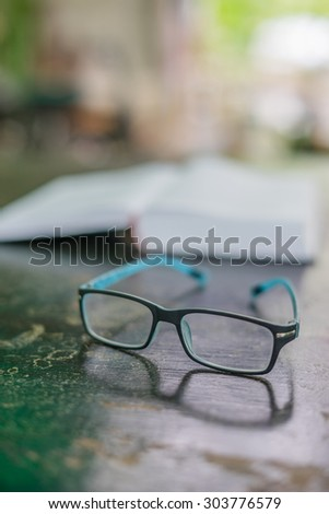 Glasses on the table and a book in information time - stock photo
