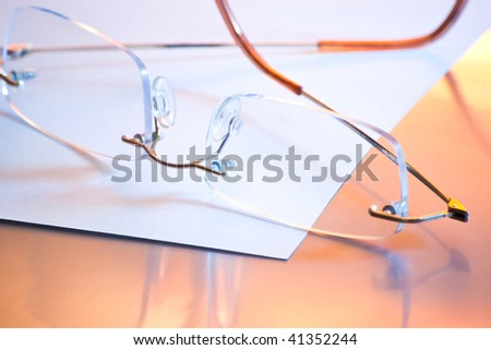 glasses on white paper in warm light