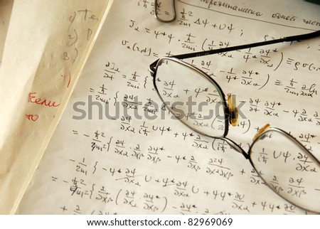 glasses over physics formulas and calculations written on paper - stock photo