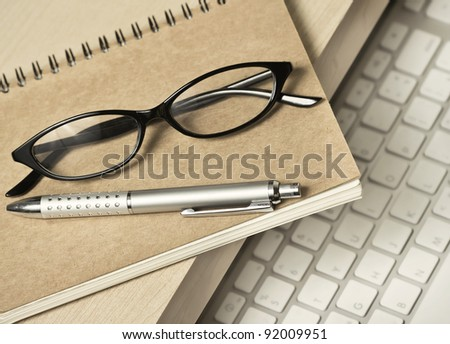 glasses, pen and book for memo on working desk - stock photo