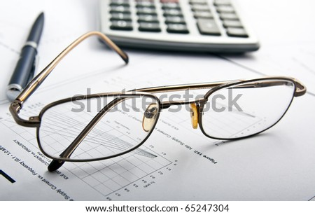 glasses, pen and calculator. Focus on glasses - stock photo